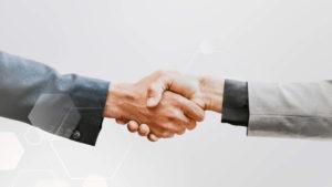 Close up of handshake on gray background.